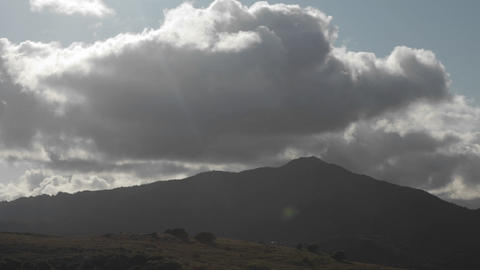 Storm clouds pass over a hilly area Footage