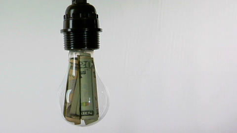 A light bulb contains twenty-dollar bills Stock Video Footage