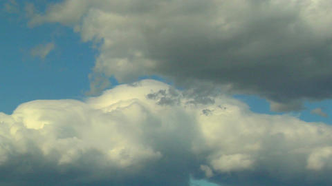 Billowy white clouds with gray undertones pass against a... Stock Video Footage