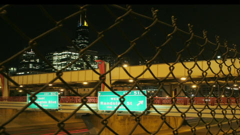 Traffic passes under a freeway overpass at night Stock Video Footage
