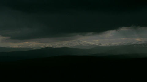 Storm clouds pass by a snow capped mountain range Stock Video Footage