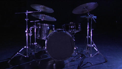 A drum set sits on a dark stage Live Action