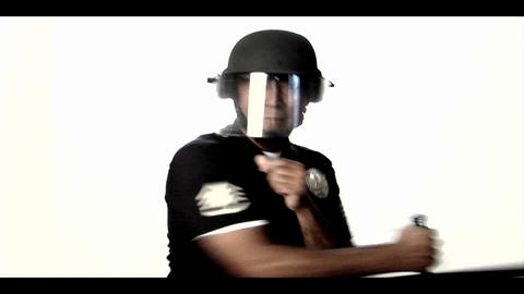 A police officer in riot gear swipes a baton back Stock Video Footage