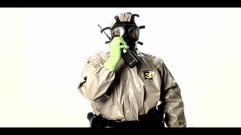 A man in a hazmat suit speaks into a walkie-talkie Footage