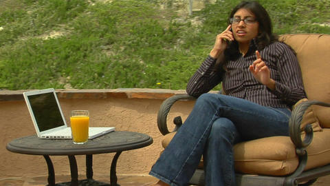 A woman speaks into a cell phone while sitting on Stock Video Footage
