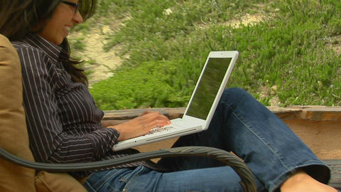 A woman on a patio sends an e-mail Live Action