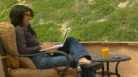A woman on a patio sends an e-mail Stock Video Footage