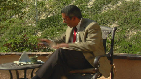 A businessman sitting on a patio becomes angry and Stock Video Footage