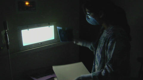 A dental hygienist looks at x-rays in a darkened r Stock Video Footage
