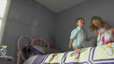 Children jump on a bed Stock Video Footage