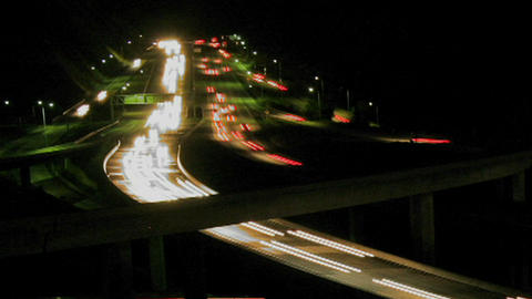 Cars drive on a freeway at night Stock Video Footage