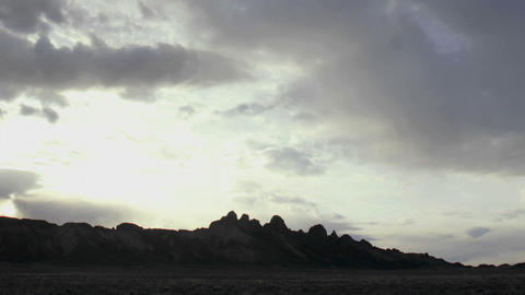 Wispy gray and white clouds pass over a mountain summit... Stock Video Footage