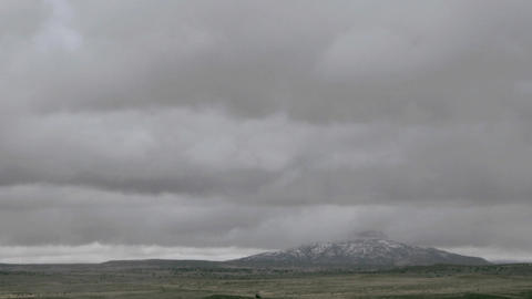 Clouds pass over a mountain on a grassy plain Stock Video Footage