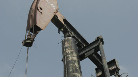 An oil pump-jack rises and falls as clouds pass across a... Stock Video Footage