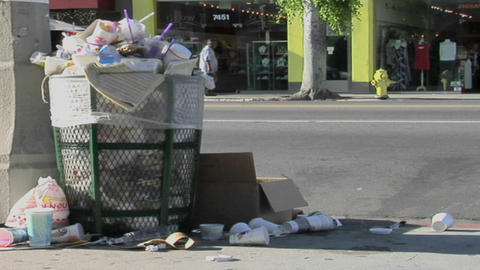 Trash spills out of an overfilled trash can on a city street Stock Video Footage