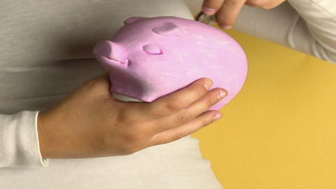 A woman places coins into a piggy bank Stock Video Footage