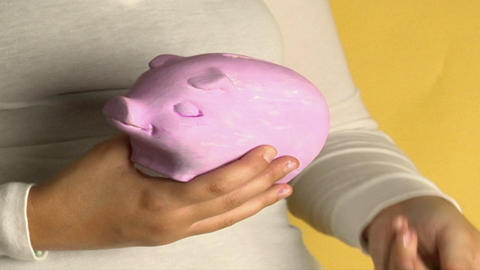 A woman places coins into a piggy bank Footage