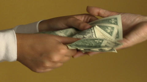 A woman pays a person with a stack of dollar bills Footage