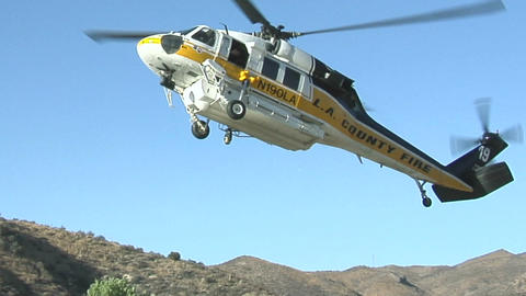 A fire fighting helicopter draws water in a mountain clearing Footage