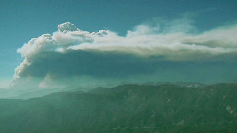 Smoke rises from a wildfire in the distant mountains Stock Video Footage
