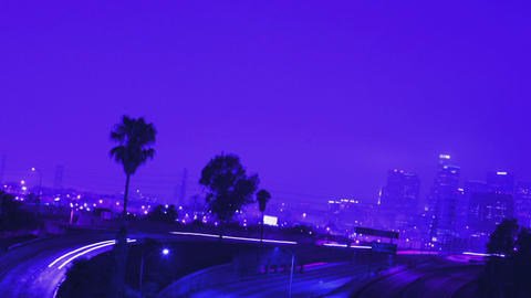 Heavy traffic drives on a busy freeway near a city at night Stock Video Footage