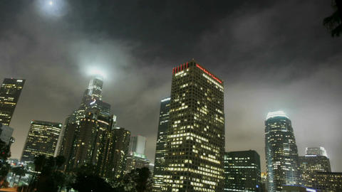 Lights illuminate high rise buildings in a downtown area at night Footage
