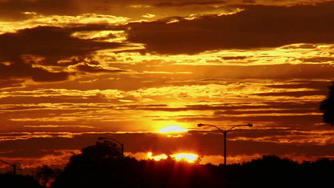 The sun glows behind clouds in a red and orange sky Stock Video Footage