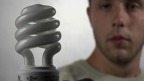 A young man gazes at a compact fluorescent light bulb as... Stock Video Footage