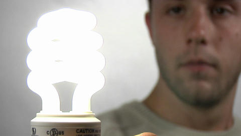 A young man gazes at a compact fluorescent light bulb as it lights Footage