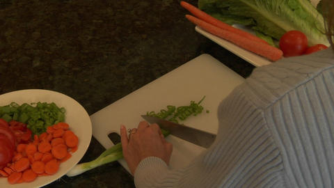 A woman chops green onions on a cutting board Footage