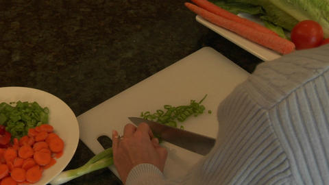 A woman chops green onions on a cutting board Stock Video Footage
