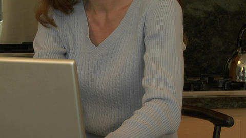 A woman sits at a kitchen counter and types on a laptop computer Footage