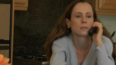 A woman holds a cell phone to her ear and listens as she sits at a kitchen counter Footage