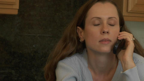 A woman holds a cell phone to her ear and listens as she... Stock Video Footage