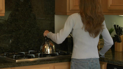 A woman sips tea at a kitchen counter Stock Video Footage