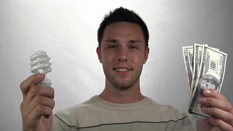 A man holds a compact-fluorescent light bulb in one hand... Stock Video Footage