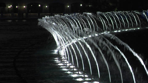 A large, animated outdoor fountain shines at night Stock Video Footage
