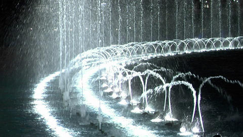 A large, animated outdoor fountain shines at night Footage
