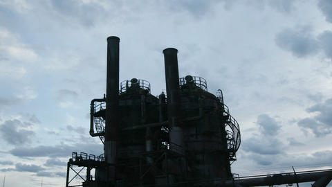 Clouds move across the sky behind an oil refinery Stock Video Footage