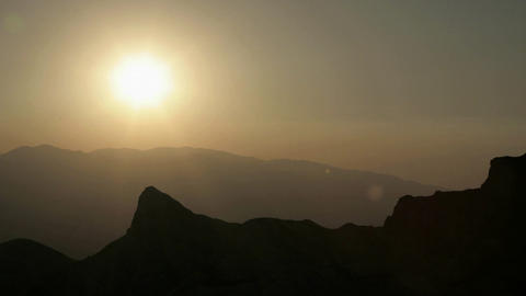 Haze hangs in a valley under an orange sky Stock Video Footage