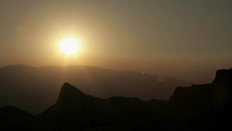 Haze hangs in a valley under an orange sky Footage