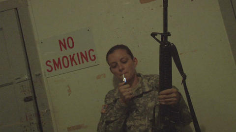 """A solider lights a cigarette in front of a No Smoking"""" sign Footage"""