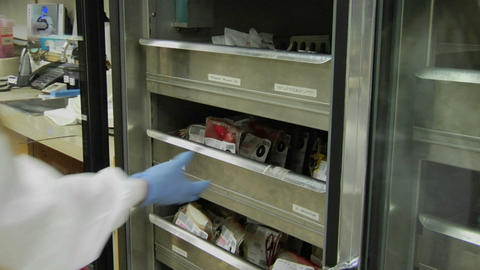 A nurse removes a bag of blood from a drawer and checks... Stock Video Footage