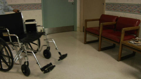 A nurse wheels an empty wheelchair through a hospital lobby Footage