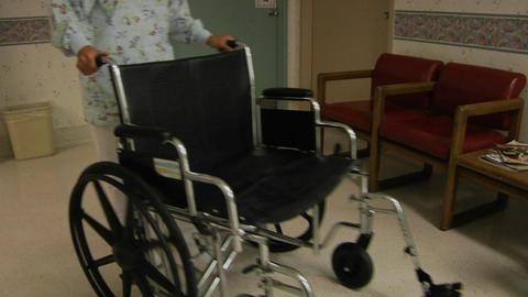 A nurse wheels an empty wheelchair through a hospital lobby Stock Video Footage