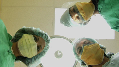 Surgeons look down on a patient Stock Video Footage