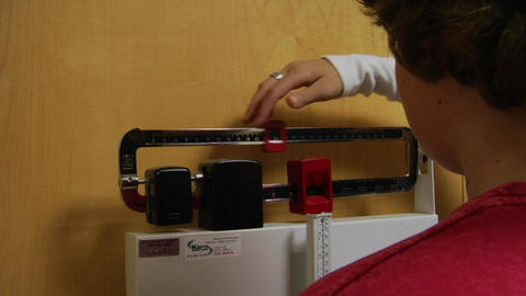 A nurse weighs a patient Footage