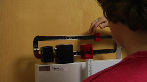 A nurse weighs a patient Stock Video Footage