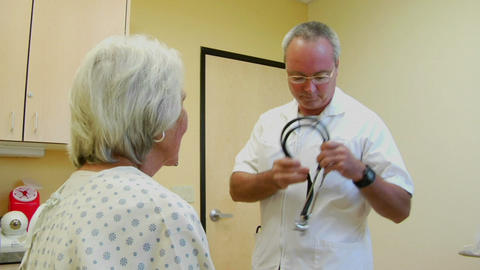 A doctor uses a stethoscope to listen to a patient's... Stock Video Footage