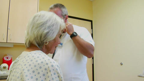 A doctor uses a stethoscope to listen to a patient's heart and lungs Footage
